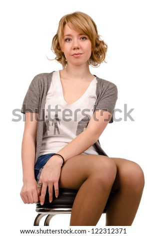 Low angle portrait of a young pretty woman with curly blonde hair sitting on a stool in shorts isolated on white