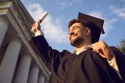 Low angle portrait of happy triumphant male graduate standing near university holding up diploma. From below of young handsome man proud of academic achievements celebrating college graduation