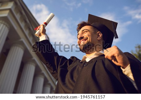 Low angle portrait of happy triumphant male graduate standing near university holding up diploma. From below of young handsome man proud of academic achievements celebrating college graduation Foto stock ©