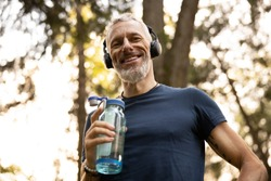 Low angle portrait of joyful grizzled athletic male drinking water while doing workout in sunny forest