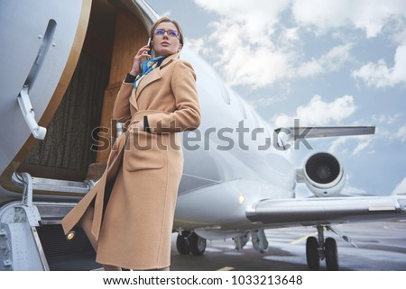 Low angle portrait of serene girl talking by phone while entering in aircraft. Career concept