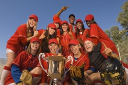 Low angle portrait of successful female softball team and coach with trophy celebrating against blue sky