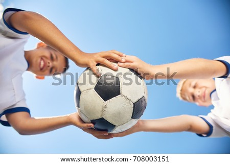Low angle portrait of two boys in junior football team holding ball against  blue sky #708003151