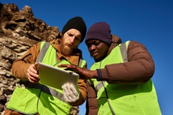 Low angle portrait of two industrial workers wearing reflective jackets, one of them African, inspecting mineral mines on worksite outdoors and using digital tablet, copy space
