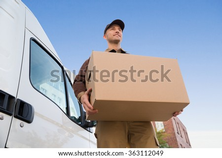 Low angle portrait of young delivery man carrying cardboard box by truck against sky #363112049