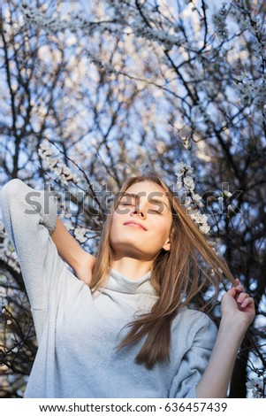 Low-angle shot beautiful woman with long blond hair posing on camera and smile. Model stands in park on blossom branches background. She dressed in white pullover. Medium Close-Up. Sunlight on face.