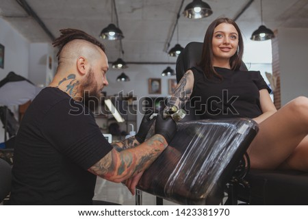 Low angle shot of a beautiful young woman getting arm sleeve tattoo by professional tattooer. Tattoo artist working at his salon, tattooing lovely female customer