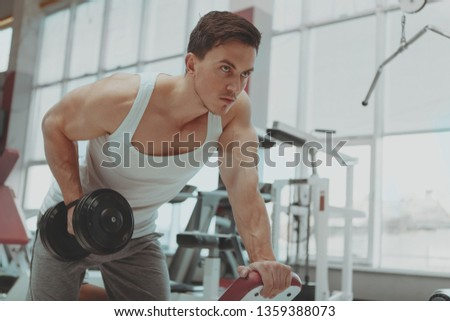 Low angle shot of a handsome muscular male athlete doing triceps exercise at the gym lifting dumbbell. Attractive focused sportsman working out with dumbbells, copy space