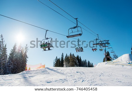 Low angle shot of a ski lift at ski resort Bukovel in the mountains on a sunny winter day. Blue sky, sun and forest on the background copyspace riding top nature extreme sport recreation concept #746405458