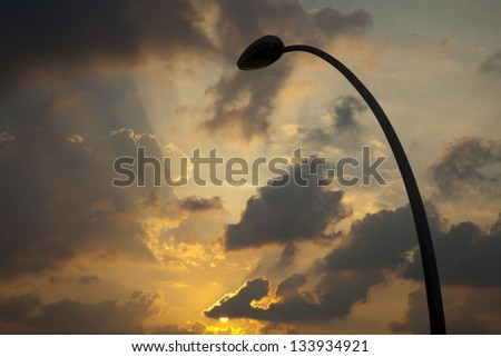 Low angle shot of a street lamp's silhouette on the background of heavily clouded dramatic winter sunset skies with the setting sun peeking from behind a cloud.