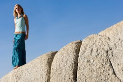 Low angle shot of a teenage girl standing atop a rock with copy space.