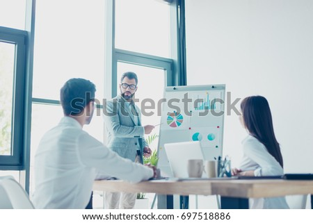 Low angle shot of a young smart brunet bearded manager in spectacles, reporting to the team of colleagues with the flip chart. Subordinates are listening to him, all dressed in formal stict outfits