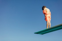 Low angle shot of boy with sleeves floats on diving board preparing for dive in the pool. Boy standing on diving spring board against sky.