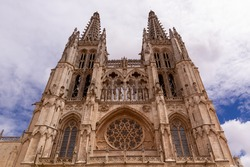 Low-angle shot of Burgos' Cathedral main facade and towers against a cloudy blue sky