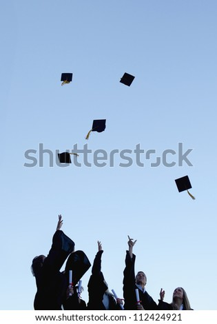 Low angle-shot of five grad students throwing their hats high in the sky
