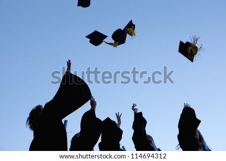 Low angle-shot of five graduates throwing their hats in the sky