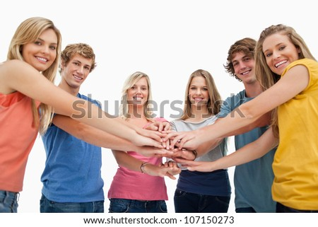 Low angle shot of friends smiling and looking at the camera with their hands stacked in the centre