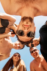 Low angle shot of happy young male and female faces, in swimwear, close up, selective focus on male face in sunglasses looking at camera. Vacation Activities, Holidays and People Concept.