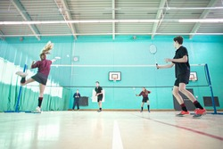 Low angle shot of high school students playing badminton during a gym class.