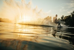 Low angle shot of man wakeboarding on a lake. Man water skiing at sunset.