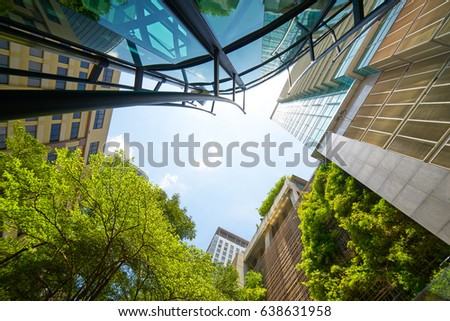 Low angle shot of modern glass buildings and green with clear sky background. #638631958