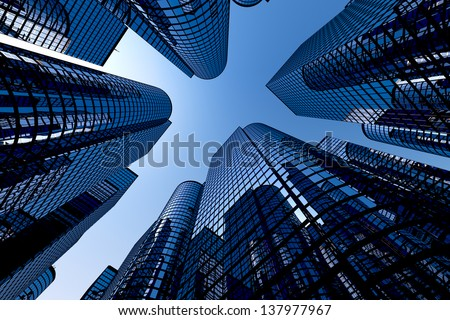Low angle shot of modern glass city buildings with clear sky background.