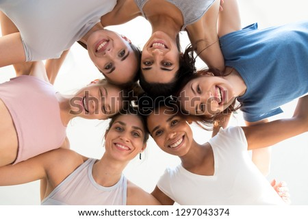 Low angle shot of multiracial excited girls stand in circle hugging looking at camera at training together, happy sportive women embrace at yoga class showing team spirit and unity. Friendship concept