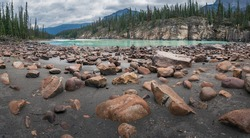 Low angle shot of sand, orange stones and cliffs in the banks of aqua-colored glacier Athabasca river not far from Athabasca Falls, Jasper National Park, AB, Canada. Cloudy day in Canadian Rockies.