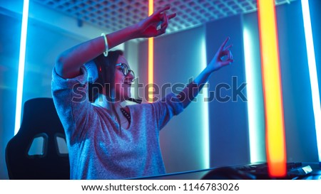 Low Angle Shot of the Beautiful Friendly Pro Gamer Girl Streaming Online Video Game and Winning it, Wearing Headset and Shares with Her Fans. Teenagers Having Fun. Background Cool Neon Retro Colors.