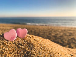 """Low angle shot of two pink candy hearts, one with the word """"love"""" on it,  on a sandy beach during the golden hour of a beautiful sunny day. The ocean is blurred in the distance."""