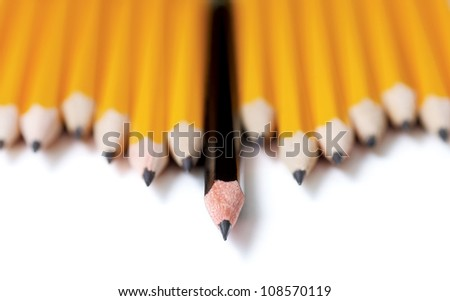 Low angle shot of Uneven row of yellow pencils with one black pencil in middle standing out farther than the rest. Focus is on the tip of the black pencil. On white with drop shadow
