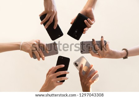 Low angle shot of women hands holding smartphones making picture or shooting video, female stand in circle using mobile phones, technology addicted girls connect to wireless network with cellphone