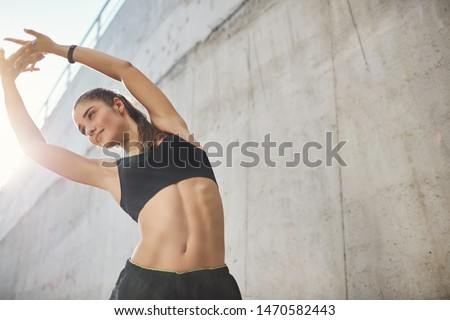 Low-angle shot pleased, motivated sporty fitness woman in sportsbra and shorts, lift hands up stretching, do morning exercise, warm-up body before marathon, smiling stand concrete wall on street