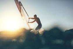 Low angle splashing view of windsurfer sailing on windsurf board. Windsurfer sailing on the surf board