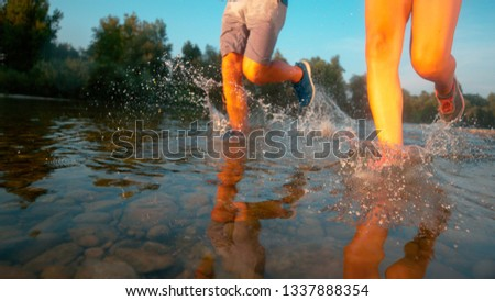 LOW ANGLE: Unrecognizable couple jogging in the shallows of a tranquil river. Fit training partners going for a relaxing jog through the scenic forest and along the refreshing stream. Fun activity #1337888354