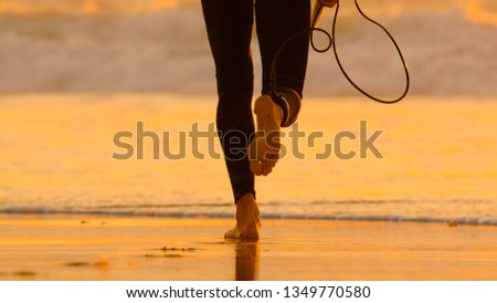 LOW ANGLE: Unrecognizable surfer in a black wetsuit running towards the foaming ocean to catch the last waves of the day. Fit man on summer vacation in Canary Islands about to go surfing at sunset. #1349770580