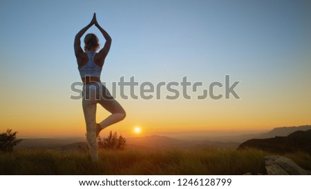 LOW ANGLE: Unrecognizable young woman standing on one leg while doing yoga at beautiful sunset in the scenic Slovenian mountains. Unknown Caucasian girl relaxing in the picturesque sunlit nature. #1246128799