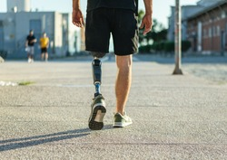 Low angle view at disabled young man with prosthetic leg walking along the street