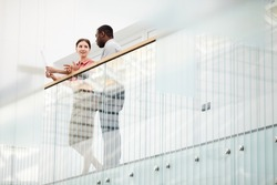 Low angle view at two contemporary business people chatting cheerfully while standing on balcony in minimal office building interior, copy space