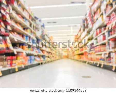 Low angle view blurred snack time, candy, chips, cookies, crackers, popcorn, nuts, rice cakes at retail store in America. Defocused snack time treats aisle on display with price tags at department.