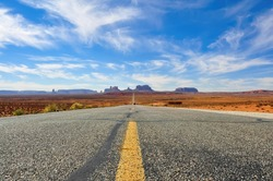 Low angle view from road level with panoramic view of Monument Valley in Utah,  United States, looking south for a long stretch on U.S. Route 163