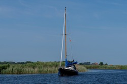 Low angle view from the water towards a sail boat cruising along one of the canals lined with reeds beds between Frisian lakes in the Netherlands with a clear blue sky