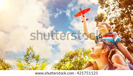 Low angle view of a boy with toy aeroplane sitting on fathers shoulders at the park