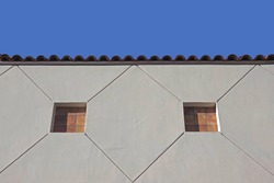 Low angle view of a building with tiled cut-outs to simulate windows and blue sky above