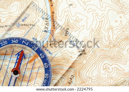 Low angle view of a compass on a topographic map pointing to a river