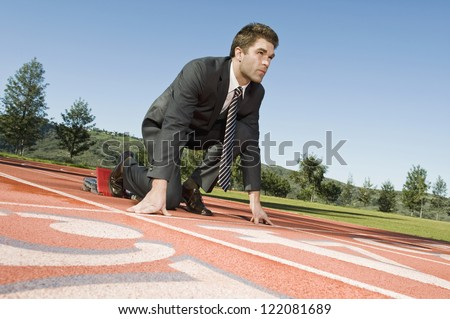 Low angle view of a confident businessman at starting position of a race track