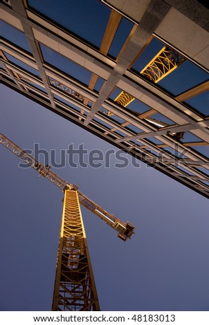 Low angle view of a crane reflected in the windows of an office building