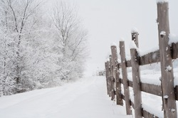 Low angle view of a festive winter wonderland snow-covered landscape, path and wooden fence.