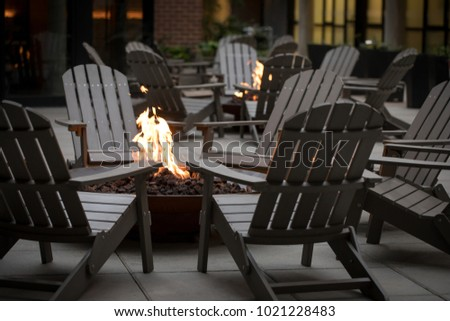 Low angle view of a fire pit surrounded by a circle of Adirondack chairs, with another campfire and hotel building in the dark background