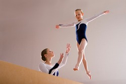 Low angle view of a gymnastics instructor teaching girl on a balance beam.